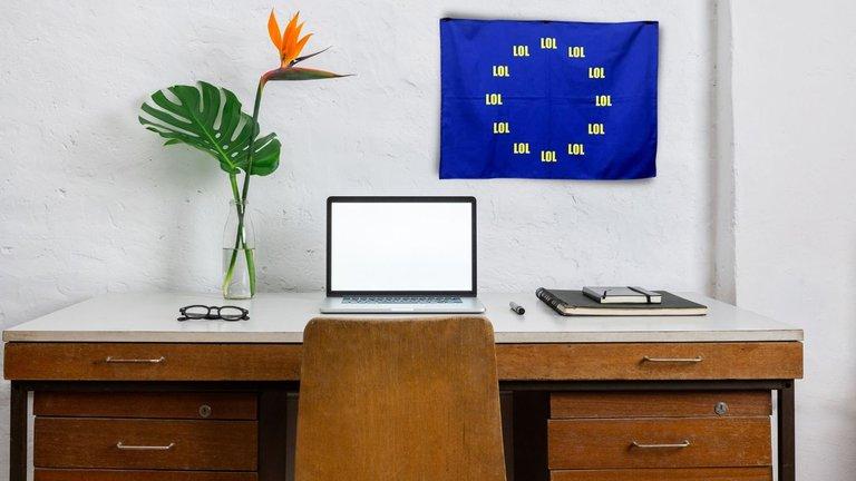 Vintage Schreibtisch mit leeren Bildschirm Laptop und LOL-EU-Flagge an der Wand