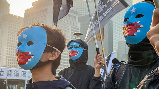 """Menschen protestieren in China mit Masken mit der in China verbotenen """"Ostturkestanflagge"""""""